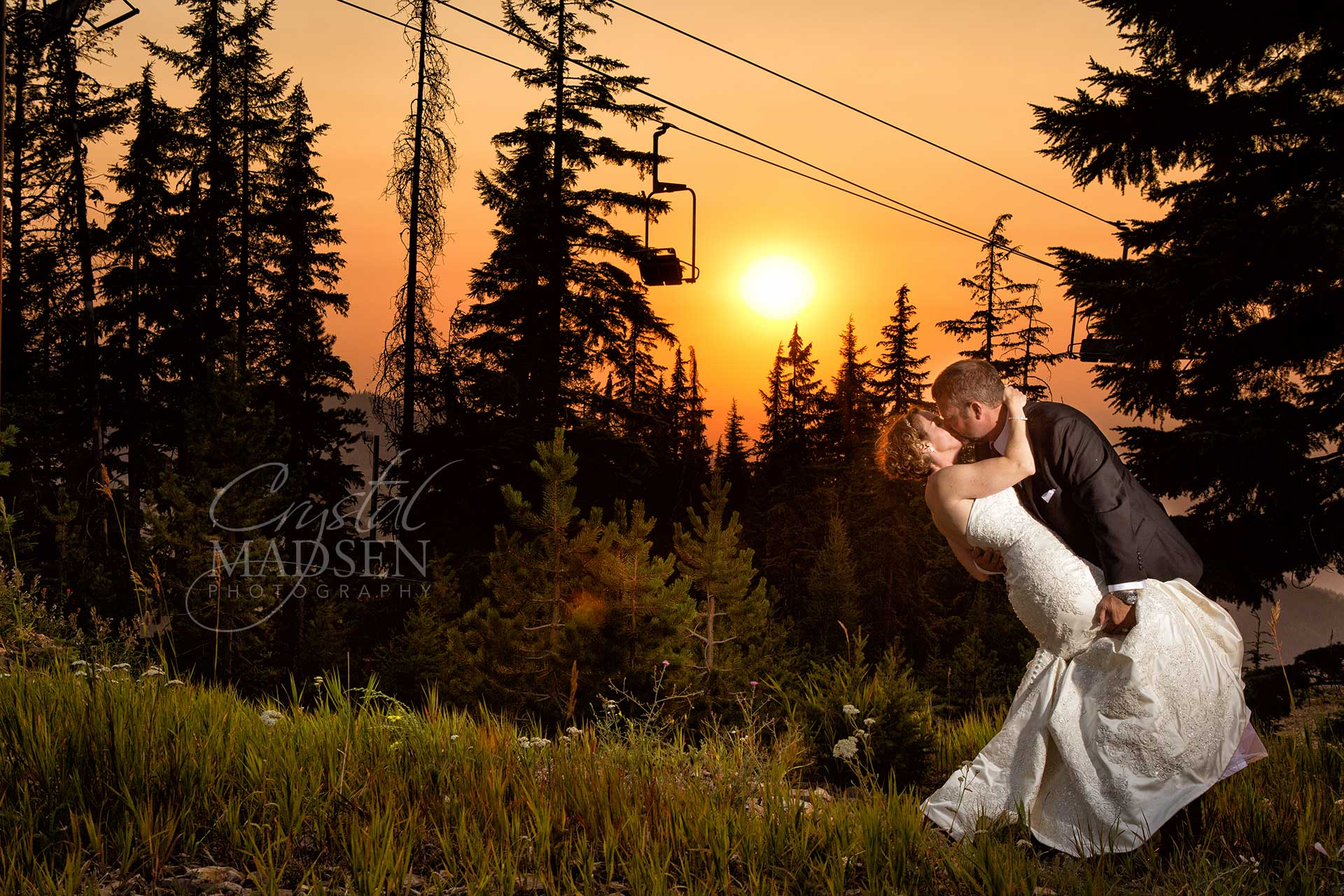 A gorgeous sunset is the backdrop for this romantic wedding photo on top of Silver Mountain